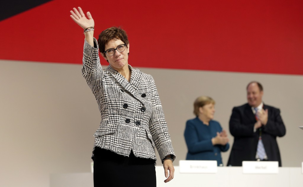 Newly elected CDU chairwoman Annegret Kramp-Karrenbauer, left, waves during the party convention of the Christian Democratic Party CDU in Hamburg, Ger