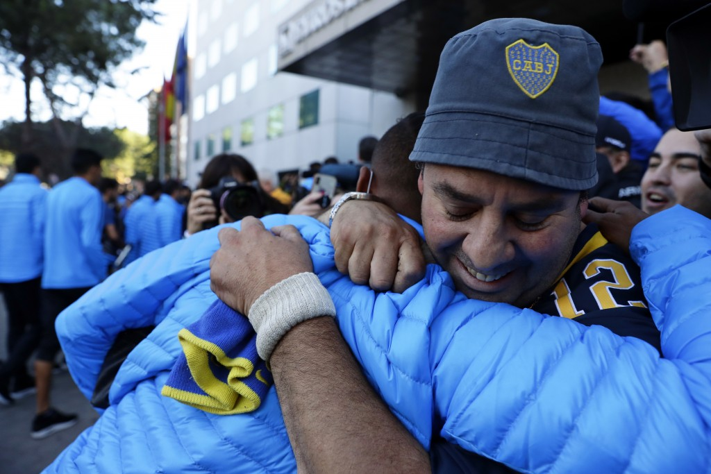 Boca Juniors' Sebastian Villa, center, is hugged by a supporter as the team arrives at their hotel in Madrid Saturday, Dec. 8, 2018. The Copa Libertad