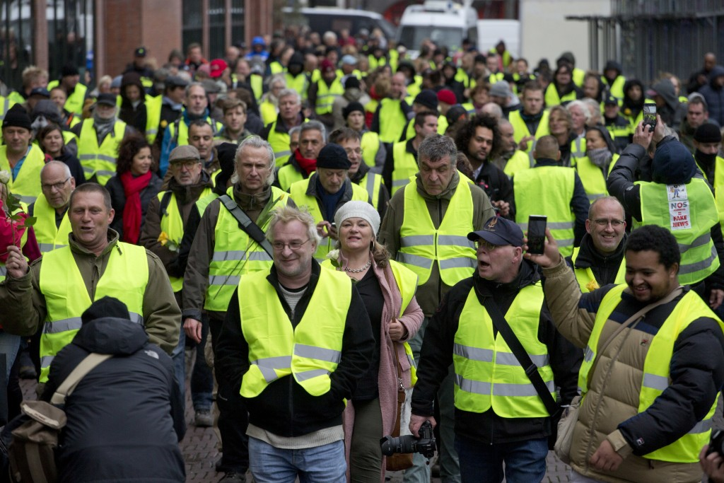 Several hundred demonstrators in yellow vests march during a peaceful demonstration in Amsterdam, Netherlands, Saturday, Dec. 8, 2018. The French yell