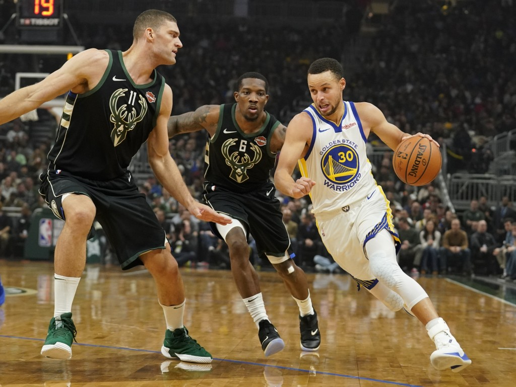 Golden State Warriors' Stephen Curry drives past Milwaukee Bucks' Eric Bledsoe and Brook Lopez during the first half of an NBA basketball game Friday,