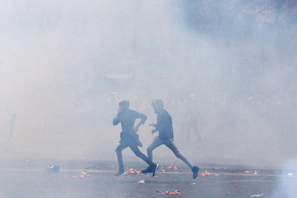 Demonstrators run away from tear gas fired by riot police during clashes in Paris, France, Saturday, Dec. 8, 2018. Crowds of protesters angry at Presi