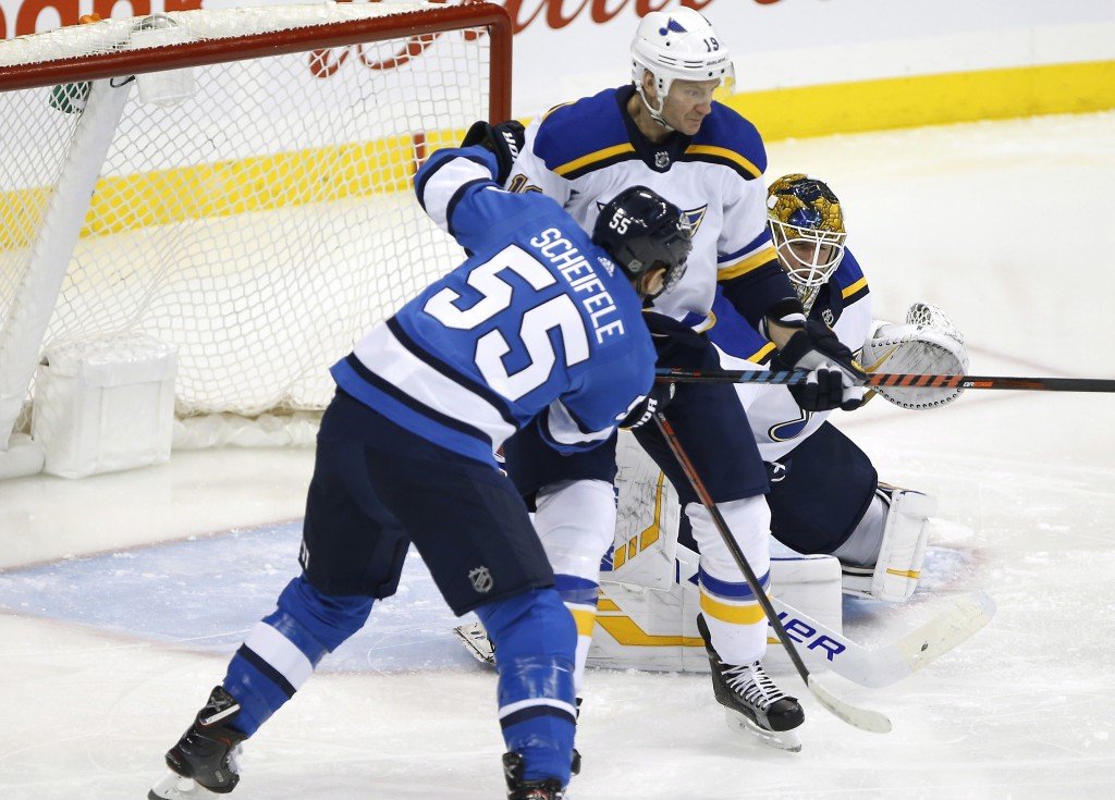 A shot by Winnipeg Jets' Mark Scheifele is stopped by St. Louis Blues goaltender Jake Allen (34) as Jay Bouwmeester (19) defends during the first peri