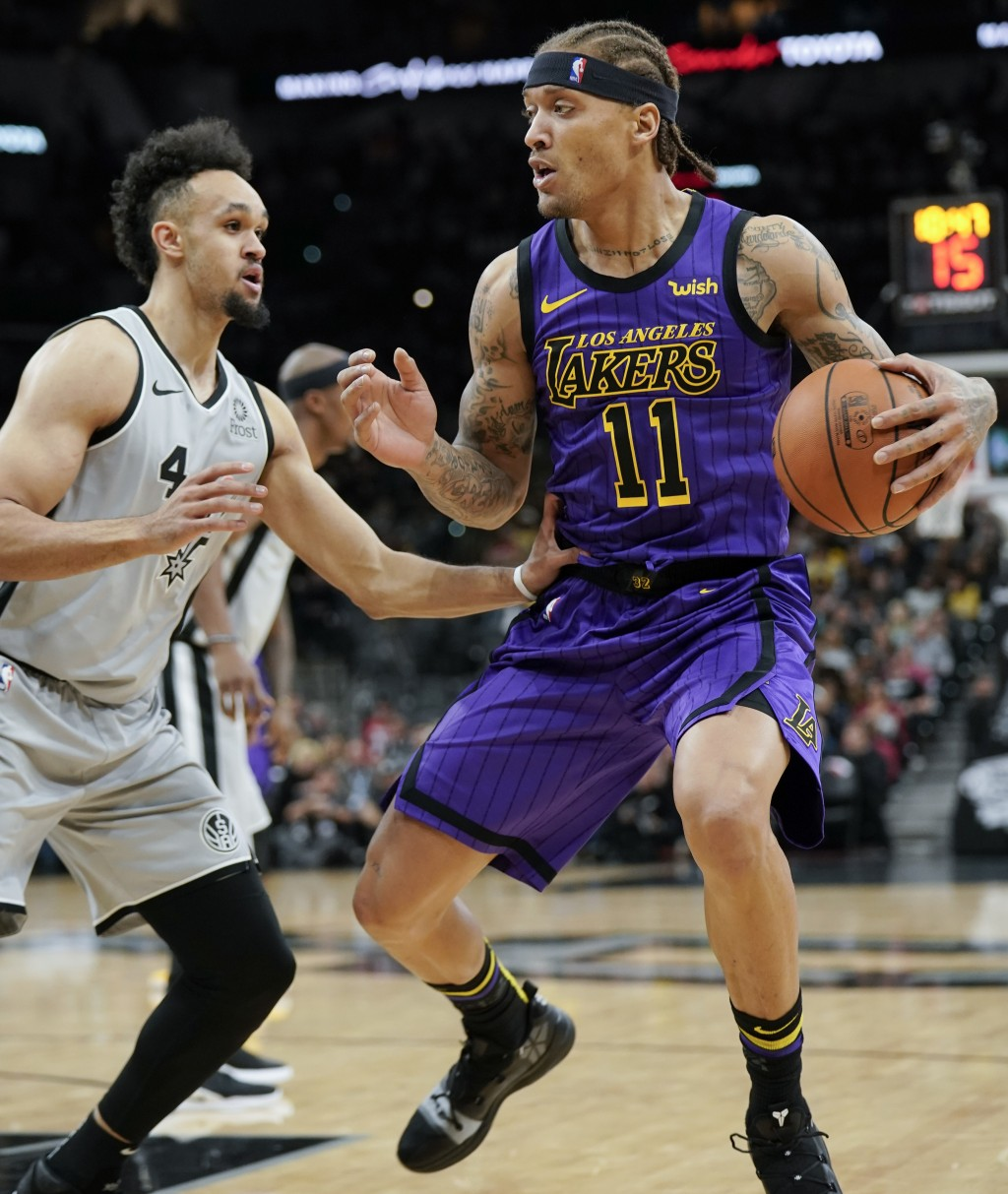 Los Angeles Lakers' Michael Beasley (11) drives against San Antonio Spurs' Derrick White during the first half of an NBA basketball game Friday, Dec.