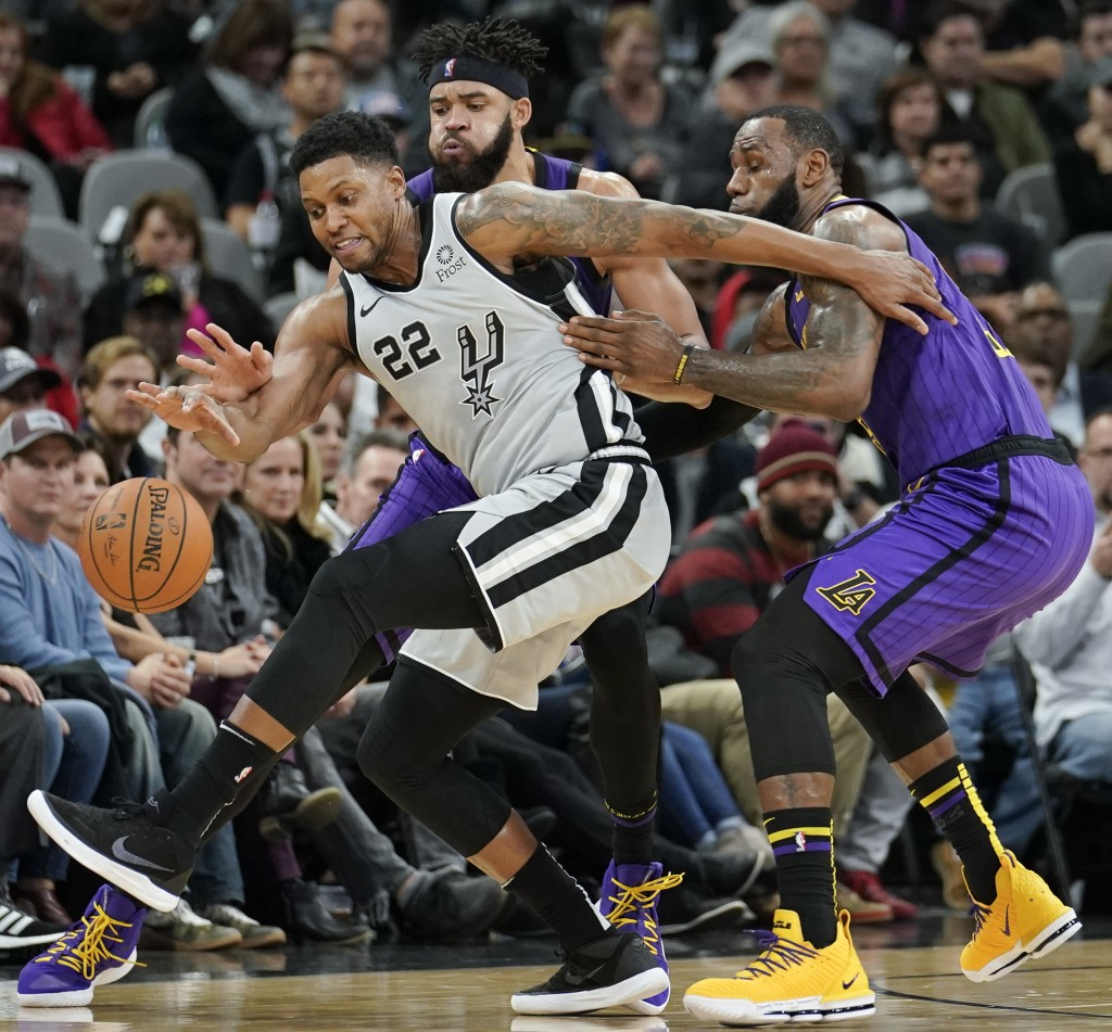 San Antonio Spurs' Rudy Gay (22) fights for the ball against Los Angeles Lakers' LeBron James, right, and JaVale McGee during the first half of an NBA