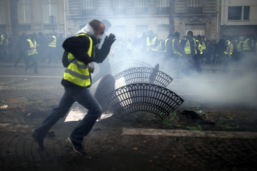 Demonstrators run away during clashes Saturday, Dec. 8, 2018 in Paris. Crowds of yellow-vested protesters angry at President Emmanuel Macron and Franc