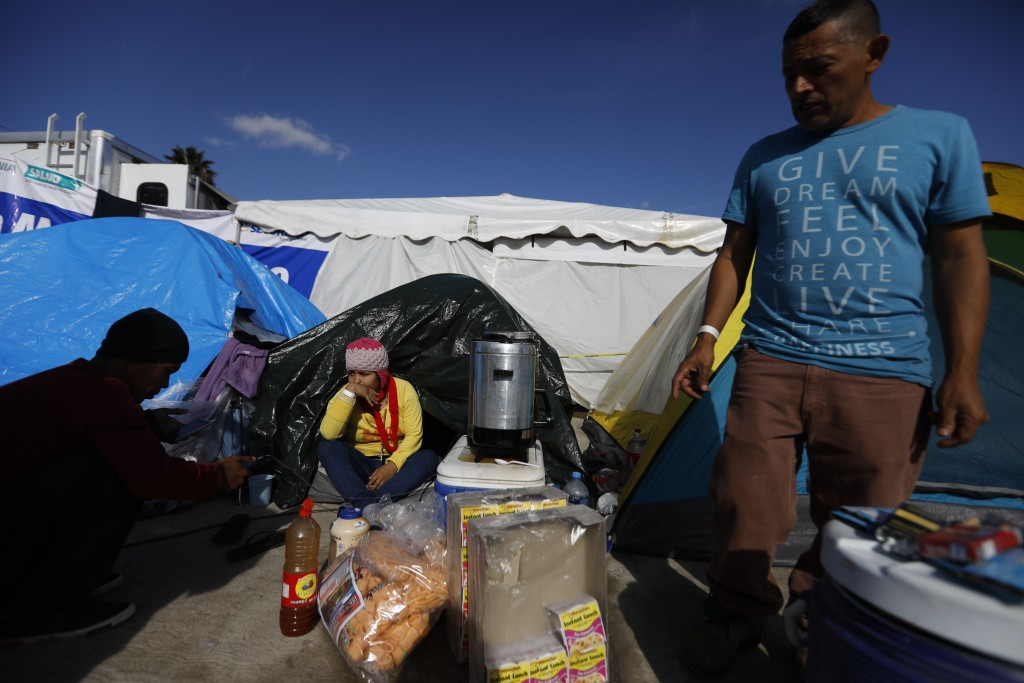 In this Dec. 2, 2018 photo, Honduran migrant Jose Daniel Castro Herrera, 44, stands next to his tent where he sells, coffee, noodles and gum inside th