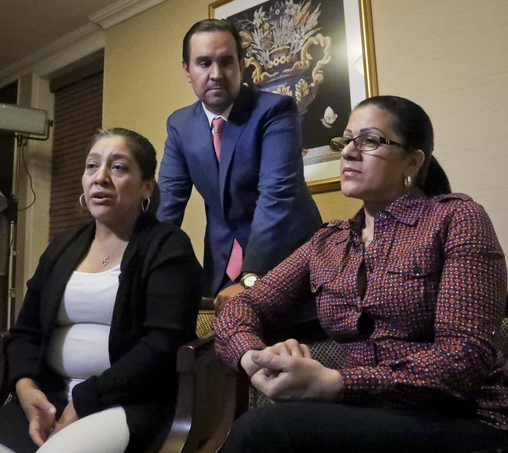 Attorney Anibal Romero, center, joins his clients Victorina Morales, left, and Sandra Diaz, right, during an interview, Friday Dec. 7, 2018, in New Yo
