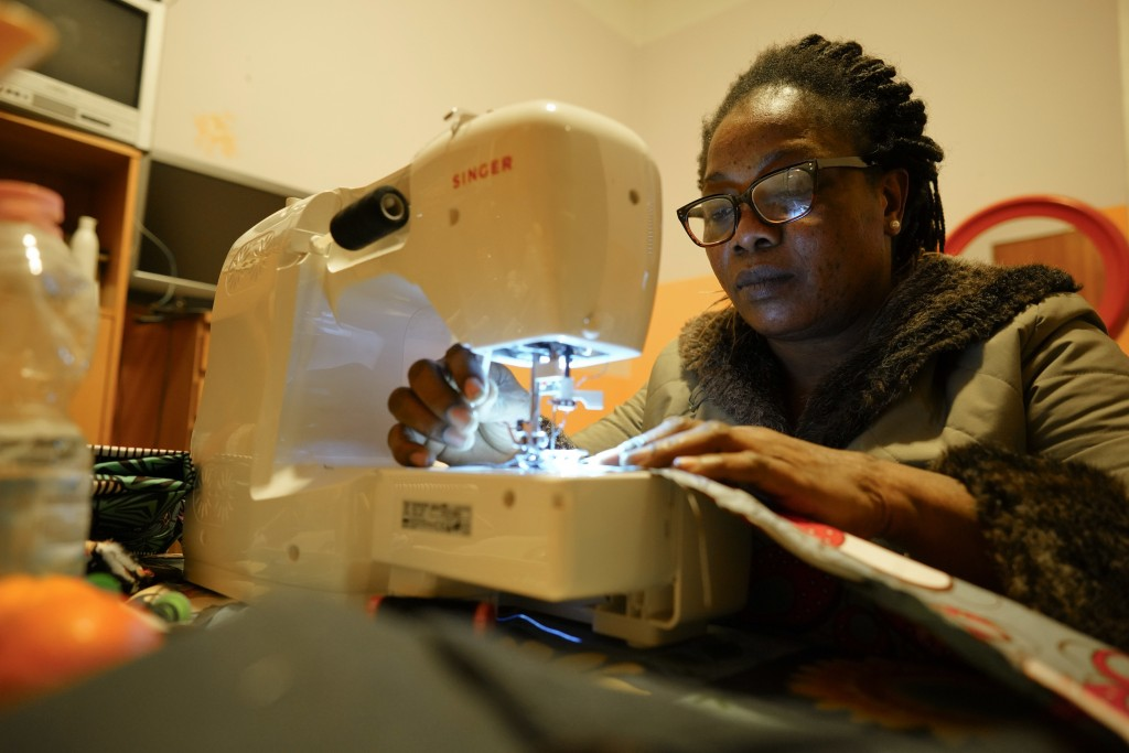 "In this photo taken on Thursday, Dec. 6, 2018, Elizabeth, from Nigeria, works at her sewing machine in the ""Well(c)home"" shelter residence for migrant"