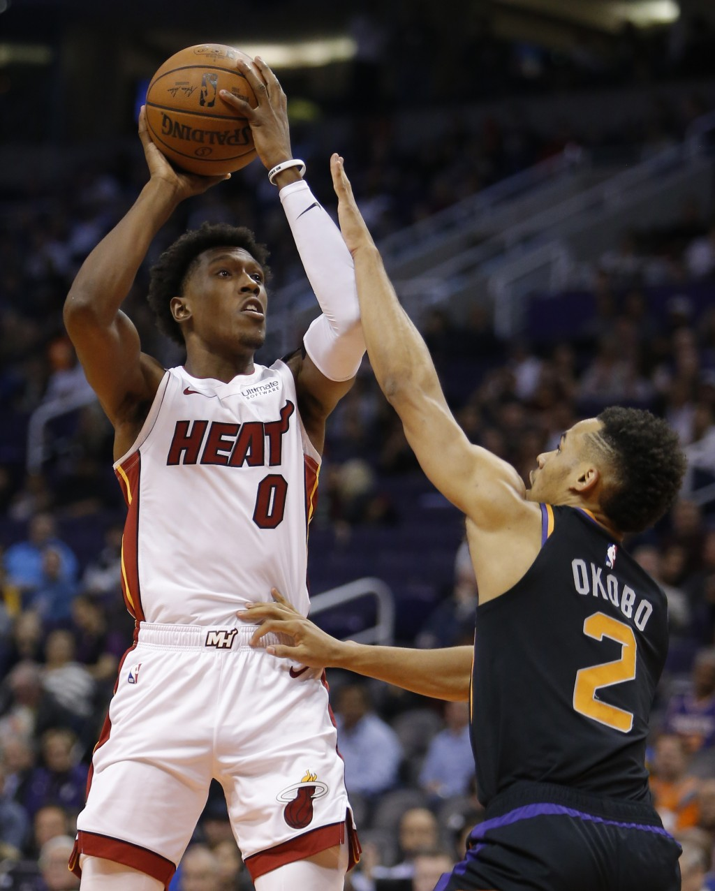 Miami Heat guard Josh Richardson (0) shoots over Phoenix Suns guard Elie Okobo during the first half of an NBA basketball game Friday, Dec. 7, 2018, i