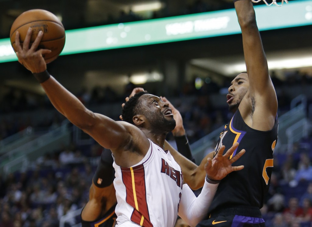 Miami Heat guard Dwyane Wade shoots in front of Phoenix Suns forward Mikal Bridges (25) during the first half of an NBA basketball game Friday, Dec. 7