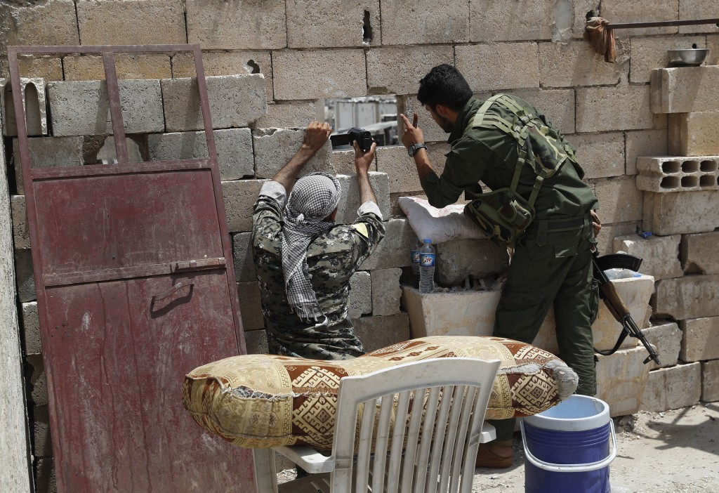 FILE - In this July 17, 2017 file photo, U.S.-backed Syrian Democratic Forces (SDF) fighters use their video camera through a hole as they film a stre