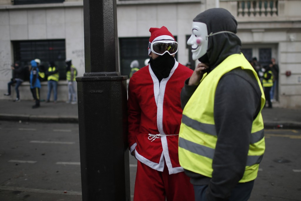 Demonstrators, one dressed like a Santa Claus, talk during clashes Saturday, Dec. 8, 2018 in Paris. Crowds of yellow-vested protesters angry at Presid