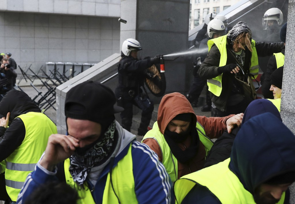 Police spray protestors with pepper spray during a demonstration in Brussels Saturday Dec. 8 2018. Hundreds of police officers are being mobilized