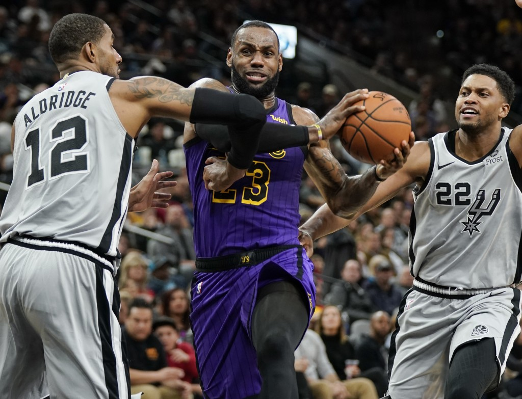 Los Angeles Lakers' LeBron James (23) drives between San Antonio Spurs' LaMarcus Aldridge (12) and Rudy Gay during the first half of an NBA basketball