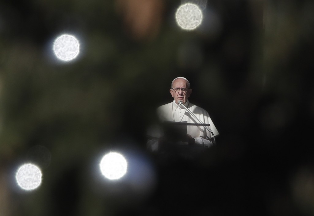 Framed by a Christmas tree, Pope Francis delivers his speech during the Angelus noon prayer he delivered from his studio window overlooking St. Peter'