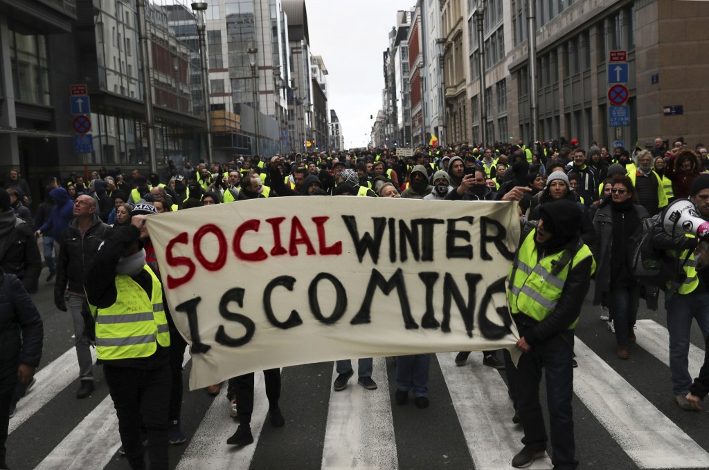 Protestors hold a banner which reads 'social winter is coming&#039 during a demonstration in Brussels Saturday Dec. 8 2018. Hundreds of police officers
