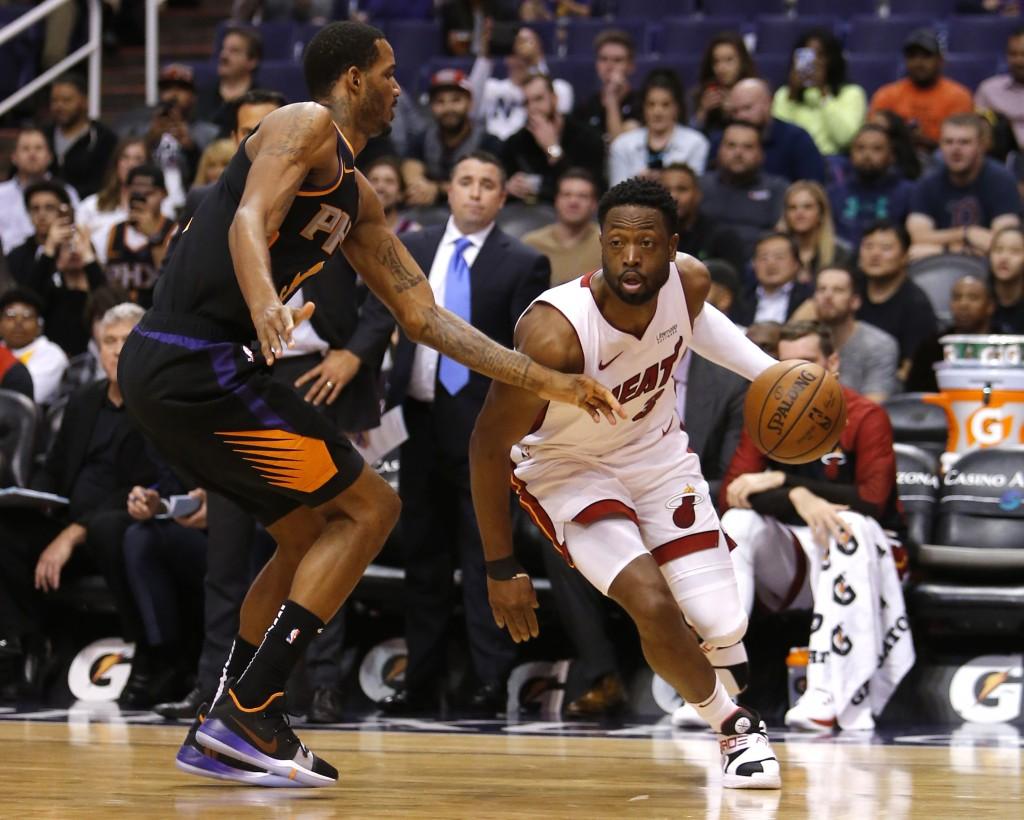 Miami Heat guard Dwyane Wade (3) drives around Phoenix Suns forward Trevor Ariza during the first half of an NBA basketball game Friday, Dec. 7, 2018,