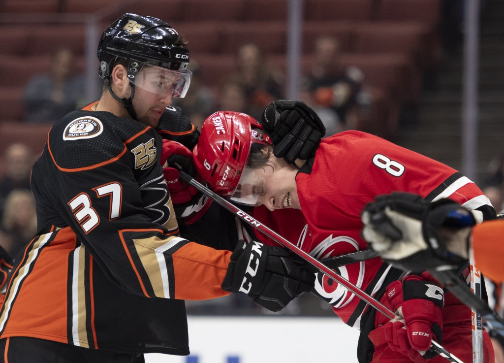 Anaheim Ducks left wing Nick Ritchie, left, pulls Carolina Hurricanes right wing Saku Maenalanen away from Anaheim Ducks goaltender John Gibson during