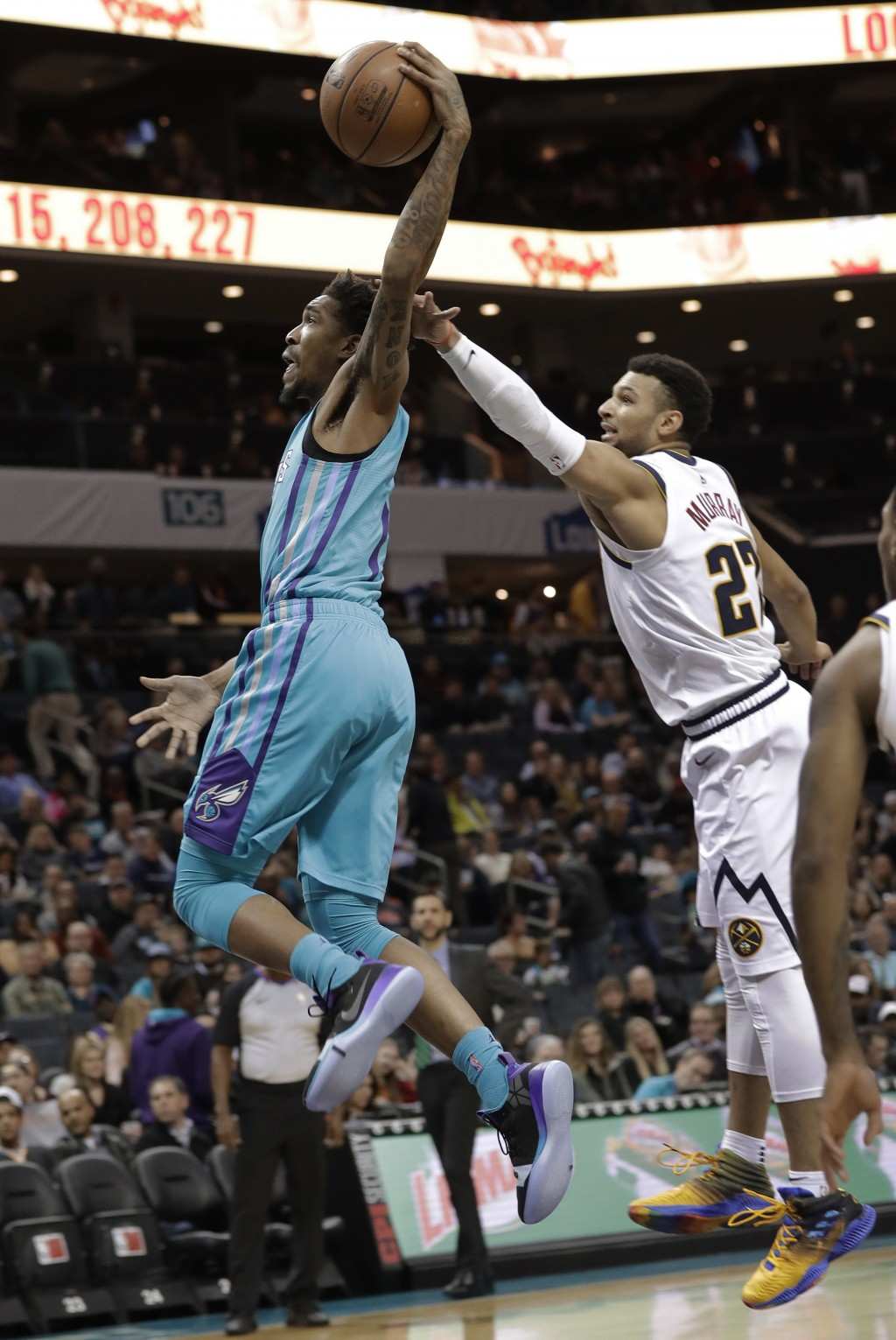 Charlotte Hornets' Malik Monk, left, drives past Denver Nuggets' Jamal Murray, right, during the first half of an NBA basketball game in Charlotte, N.