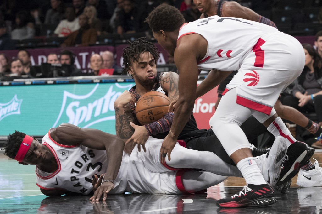 Brooklyn Nets guard D'Angelo Russell, center, vies for the ball against Toronto Raptors forward Pascal Siakam (43) and guard Kyle Lowry (7) during the