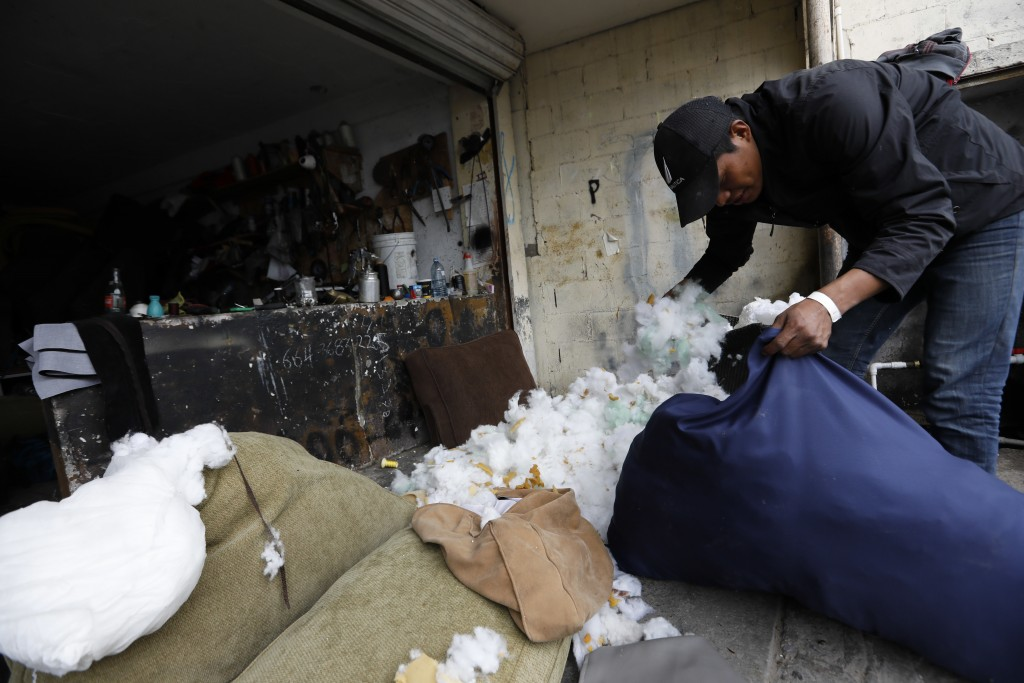 In this Dec. 5, 2018 photo, Honduran migrant Jose Perez, 22, stuffs a pillow as he works as a day laborer at an upholstery shop in Tijuana, Mexico. Me