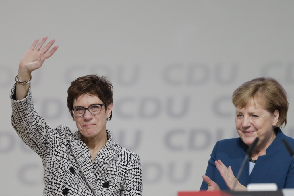 German Chancellor Angela Merkel, right, applauds newly elected party chairwoman Annegret Kramp-Karrenbauer after the election at the party convention