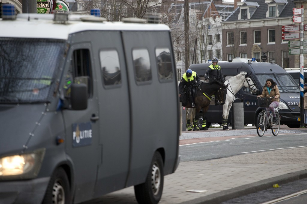 Dutch police keeps a distance as several hundred demonstrators in yellow vests march during a peaceful demonstration in Amsterdam, Netherlands, Saturd