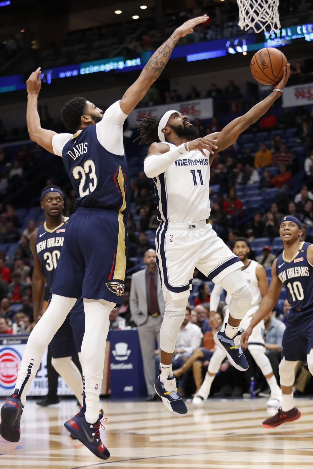 Memphis Grizzlies guard Mike Conley (11) goes up to shoot in front of New Orleans Pelicans forward Anthony Davis (23) in the first half of an NBA bask