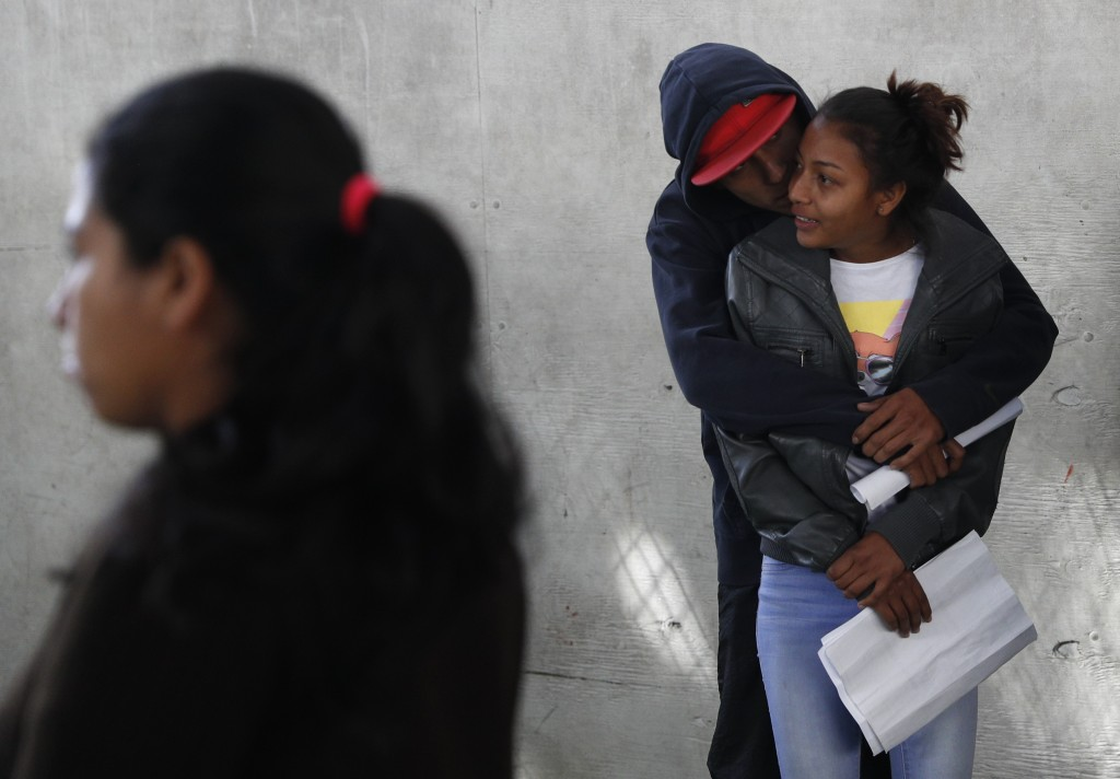 In this Dec. 4, 2018 photo, a couple embraces as they wait in line at a job fair where migrants are able to apply for Mexican work permits, recover lo