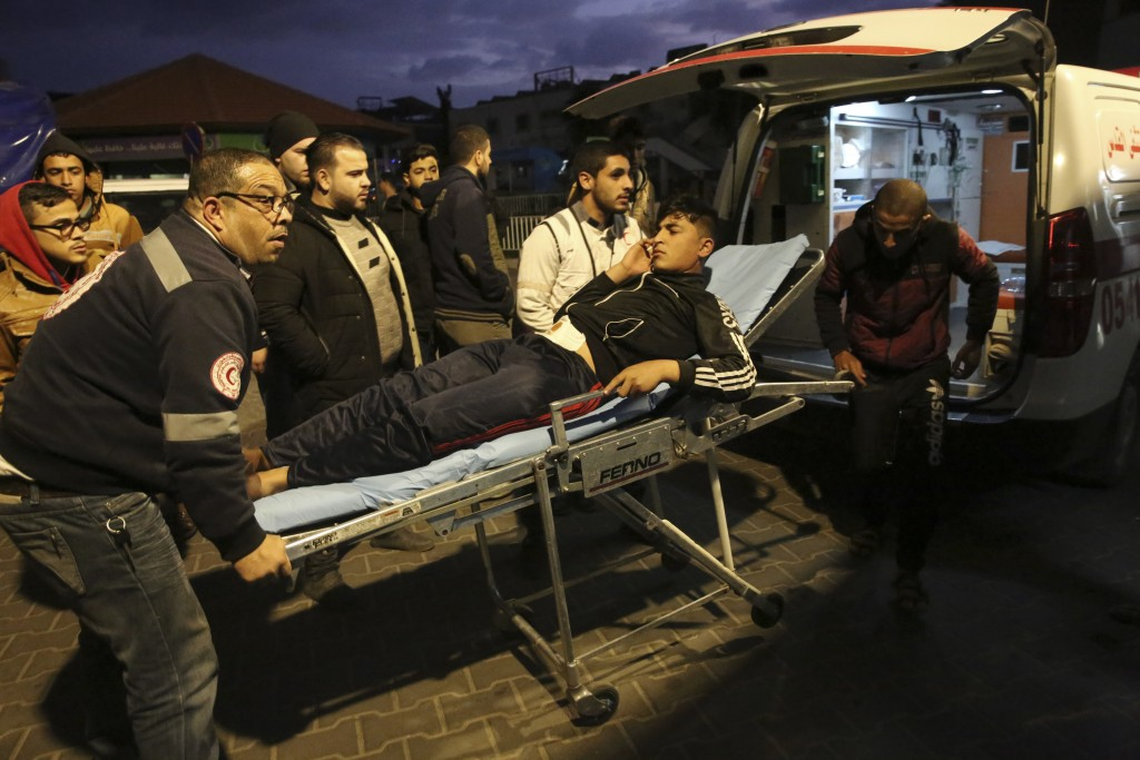 Palestinian medics move a wounded youth who was shot by Israeli troops during a protest at the Gaza Strip's border with Israel, at the Shifa hospital