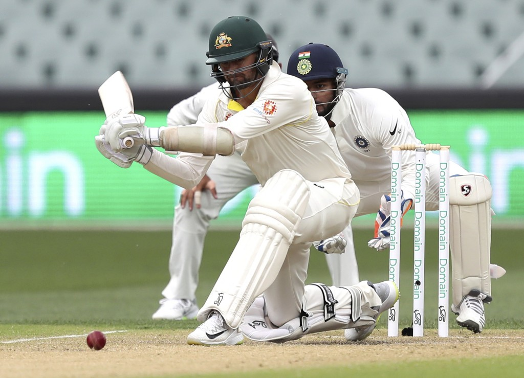 Australia's Nathan Lyon looks to play a sweep shot while batting during the first cricket test between Australia and India in Adelaide, Australia,Satu