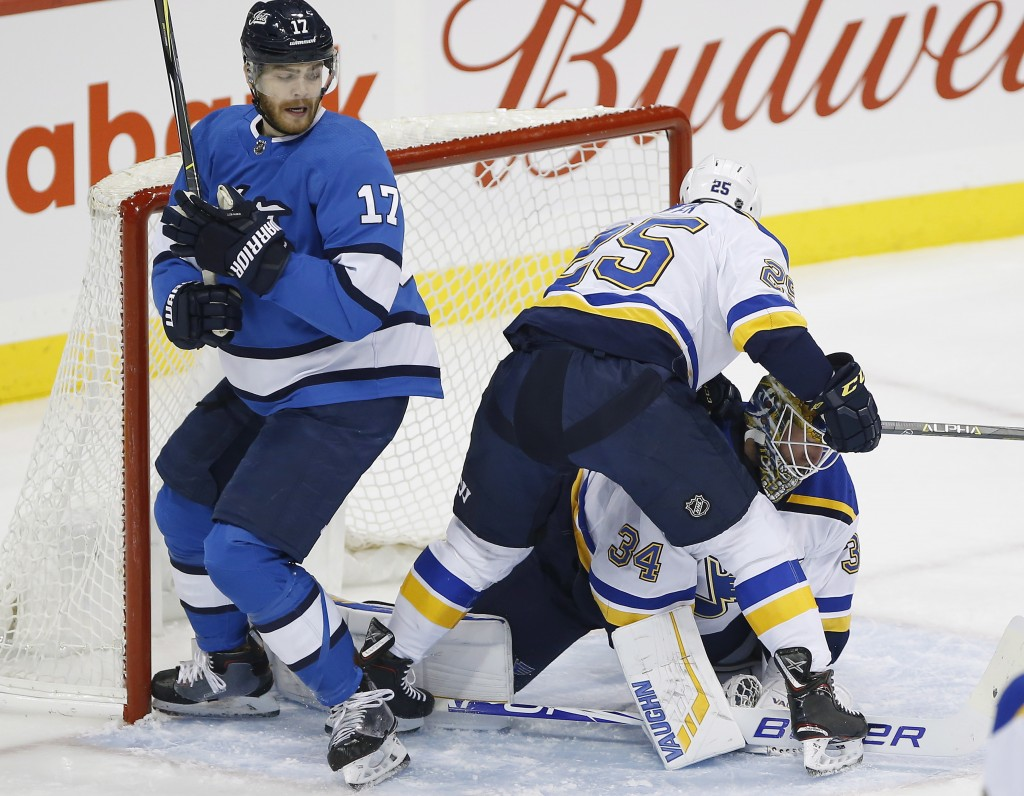 St. Louis Blues goaltender Jake Allen (34) jumps on the loose puck as Blues' Chris Butler (25) defends against Winnipeg Jets' Adam Lowry (17) during t