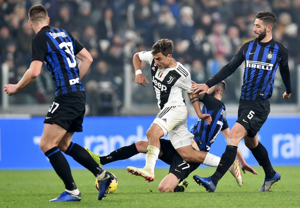 Juventus' Paulo Dybala is challenged by Inter's Roberto Gagliardini, right, during the Serie A soccer match between Juventus and Inter Milan at the Tu