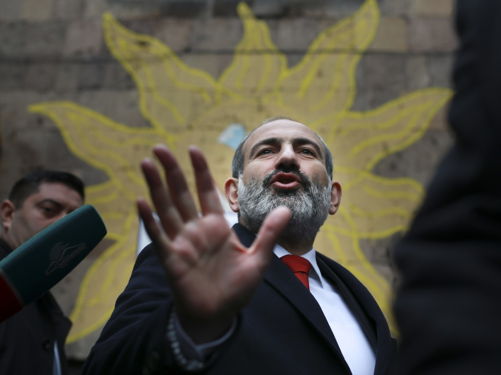 Acting Armenian Prime Minister Nikol Pashinian gestures as he leaves a polling station during an early parliamentary election in Yerevan, Armenia, Sun
