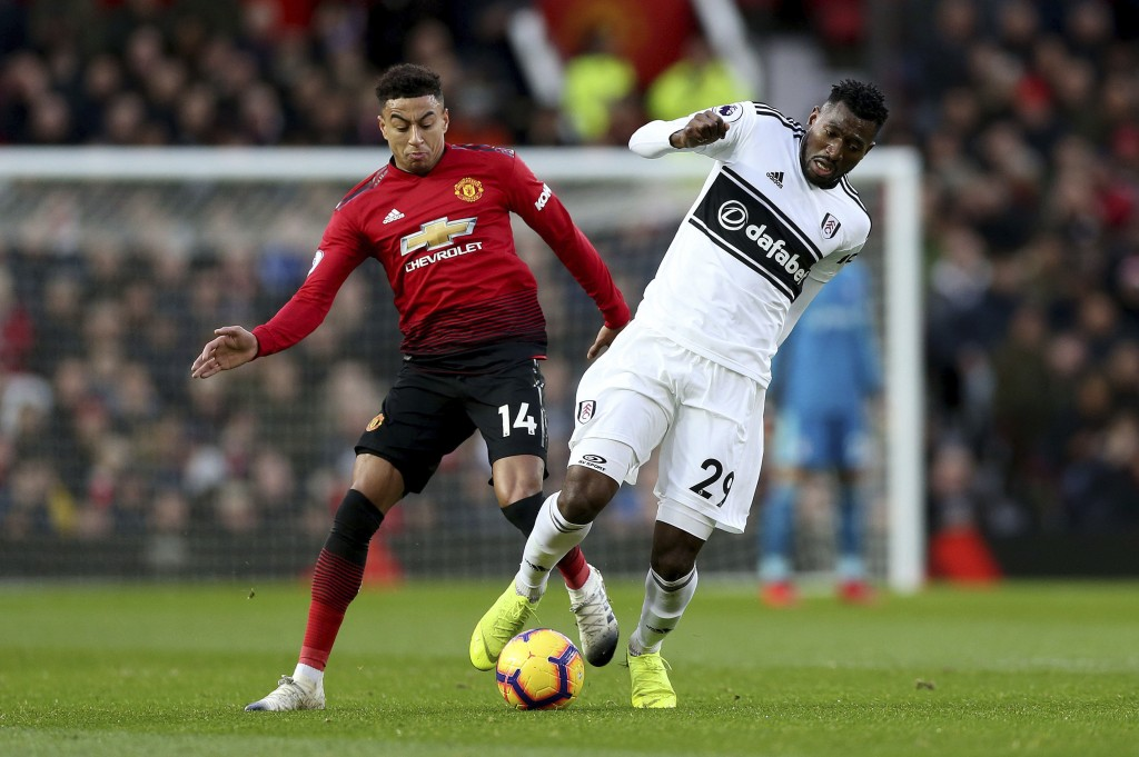 Manchester United's Jesse Lingard, left, and Fulham's Andre-Frank Zambo Anguissa in action during their English Premier League soccer match at Old Tra