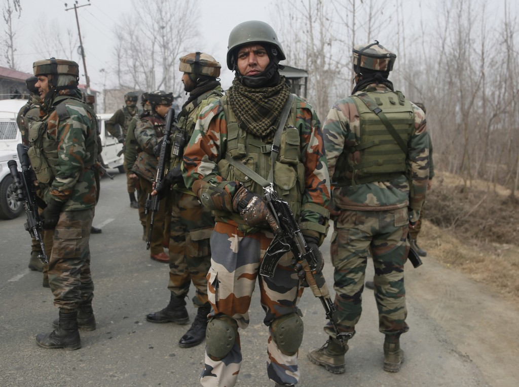 Indian soldiers stand guard near the site of a gun-battle in Mujagund area some 25 Kilometers (16 miles) from Srinagar, Indian controlled Kashmir, Sun