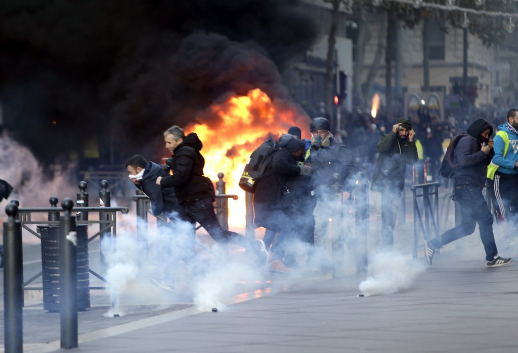 People run away from a burning car during clashes, Saturday, Dec. 8, 2018 in Marseille, southern France. The grassroots movement began as resistance a