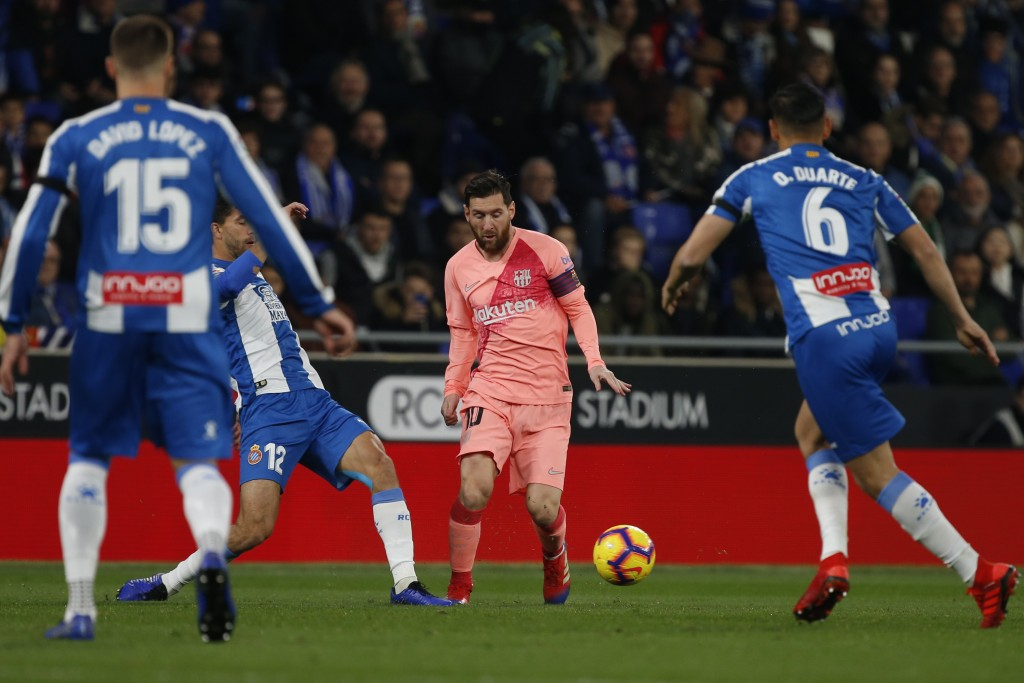 FC Barcelona's Lionel Messi, centre,  kicks the ball during the Spanish La Liga soccer match between Espanyol and FC Barcelona at RCDE stadium in Corn