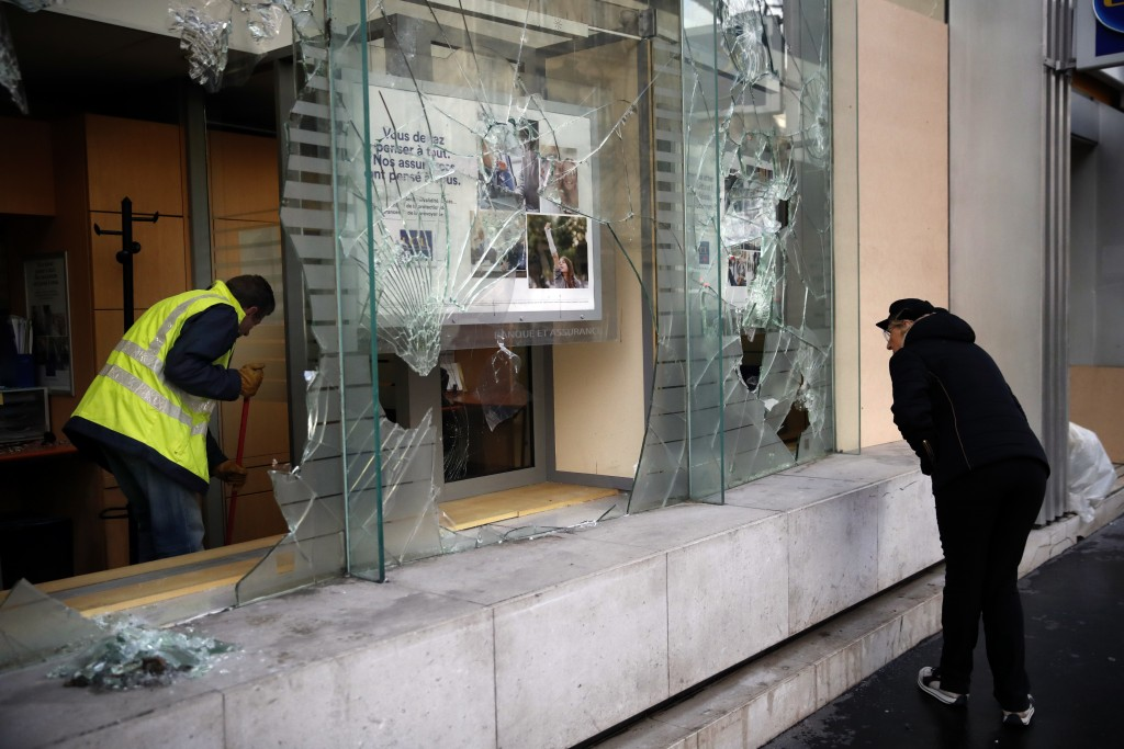 A worker clears debris in a bank as a man watches through smashed windows, in Paris, Sunday, Dec. 9, 2018. Paris monuments reopened, cleanup workers c