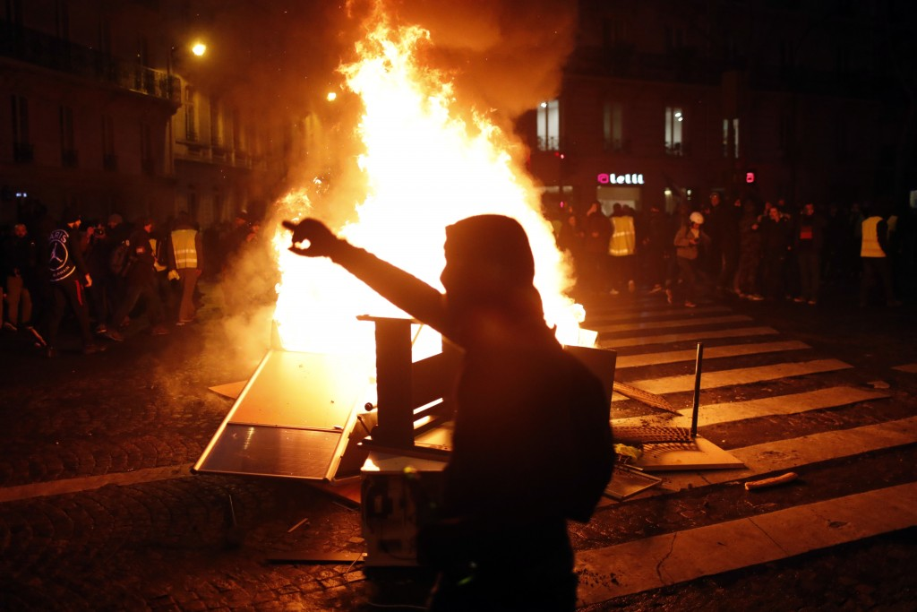 Demonstrators gather around a burning barricade during clashes with riots police, in Paris, France, Saturday, Dec. 8, 2018. Crowds of protesters angry