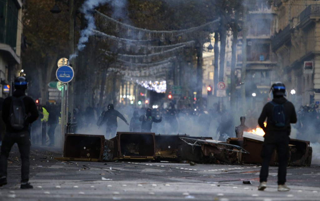 Demonstrators stand behind a burning barricade during clashes, Saturday, Dec. 8, 2018 in Marseille, southern France. The rumble of armored police truc