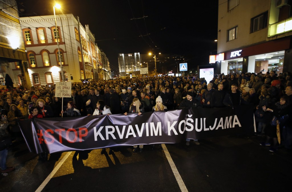 People hold a banner that reads: ''Stop to bloody shirts'' during a protest in Belgrade, Serbia, Saturday, Dec. 8, 2018. Thousands of people marched i