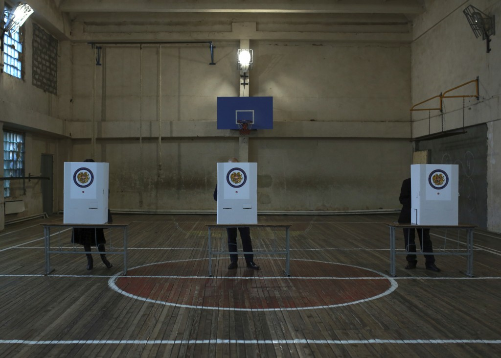 Armenians fill their ballot papers at a polling station during an early parliamentary election in Yerevan, Armenia, Sunday, Dec. 9, 2018. The charisma