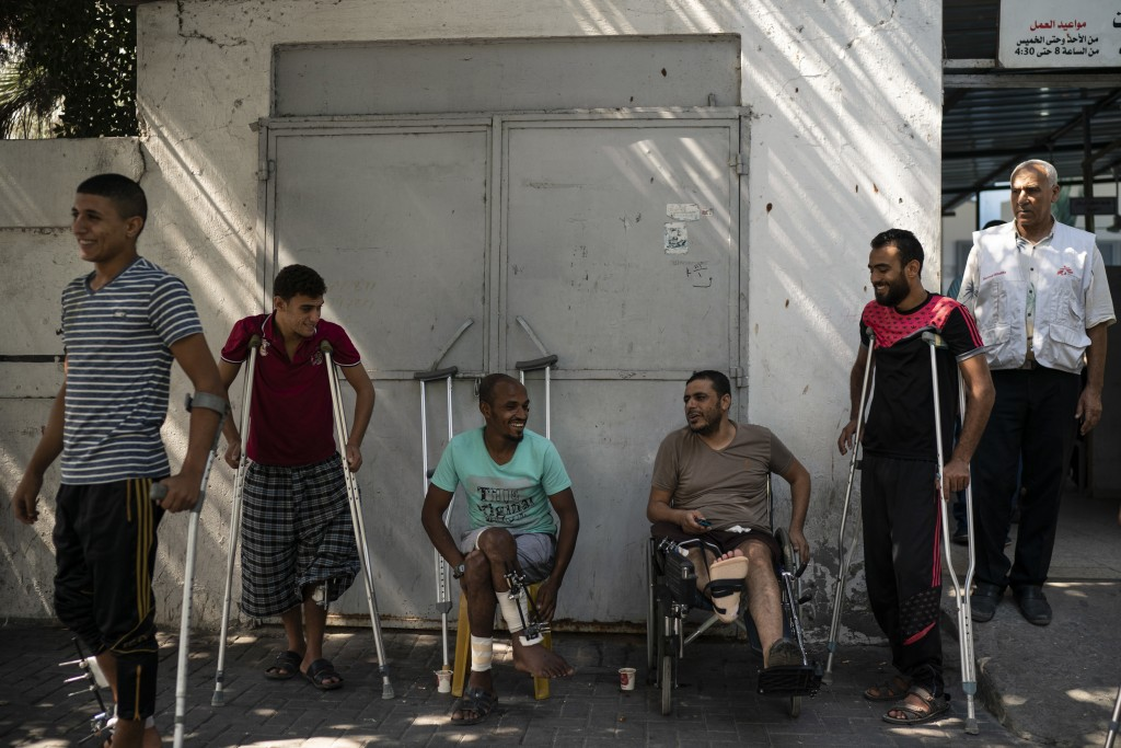 In this Sept. 10, 2018, photo, patients with leg injuries they attained during demonstrations, gather outside a clinic run by MSF (Doctors Without Bor...