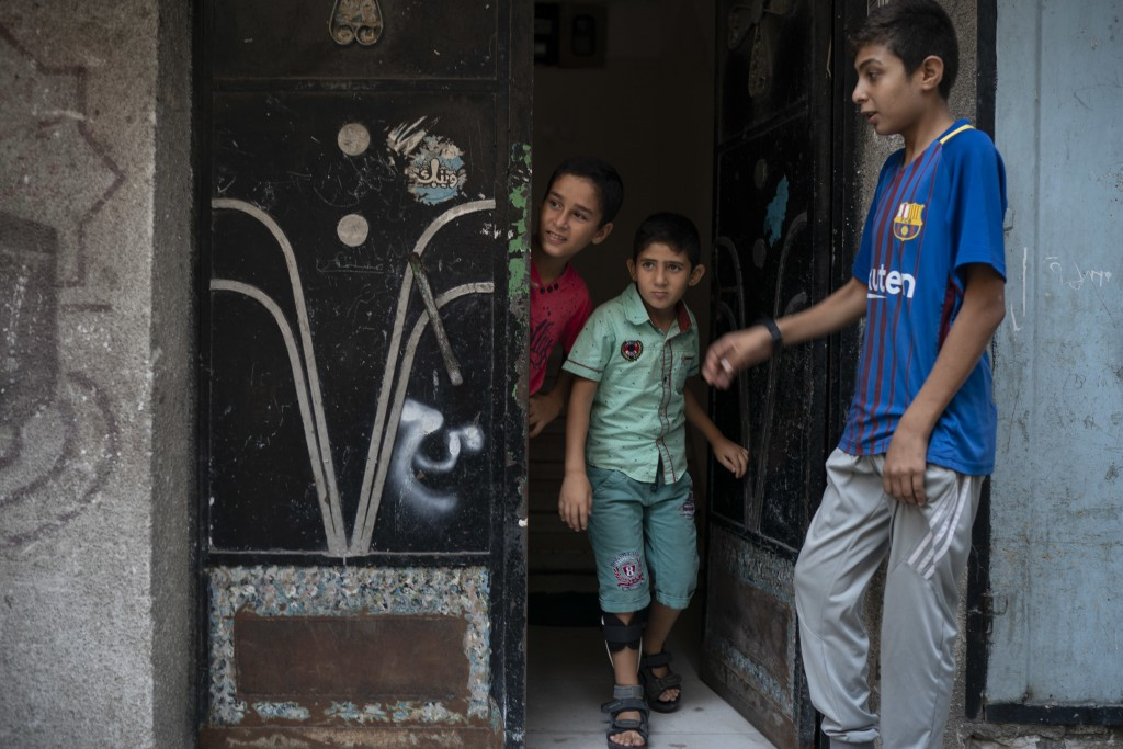 In this Sept. 16, 2018, photo, 8-year-old Mohamed al-Dalo, center, who was shot in the leg during a demonstration, stands at the entrance of his house...