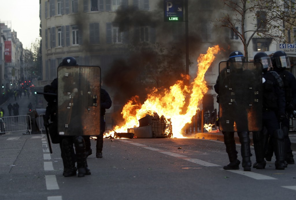 Riot police officer stand in front a burning trash bin during clashes, Saturday, Dec. 8, 2018 in Marseille, southern France. French riot police fired