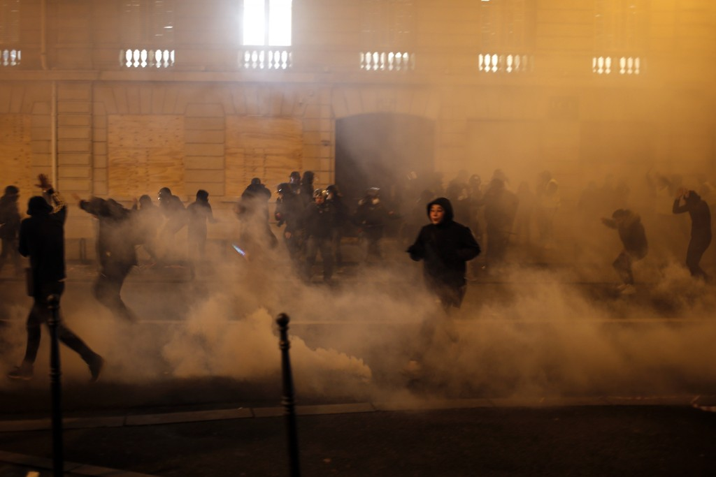 Demonstrators run away to avoid tear gas during clashes Saturday, Dec. 8, 2018 in Paris. Crowds of yellow-vested protesters angry at President Emmanue