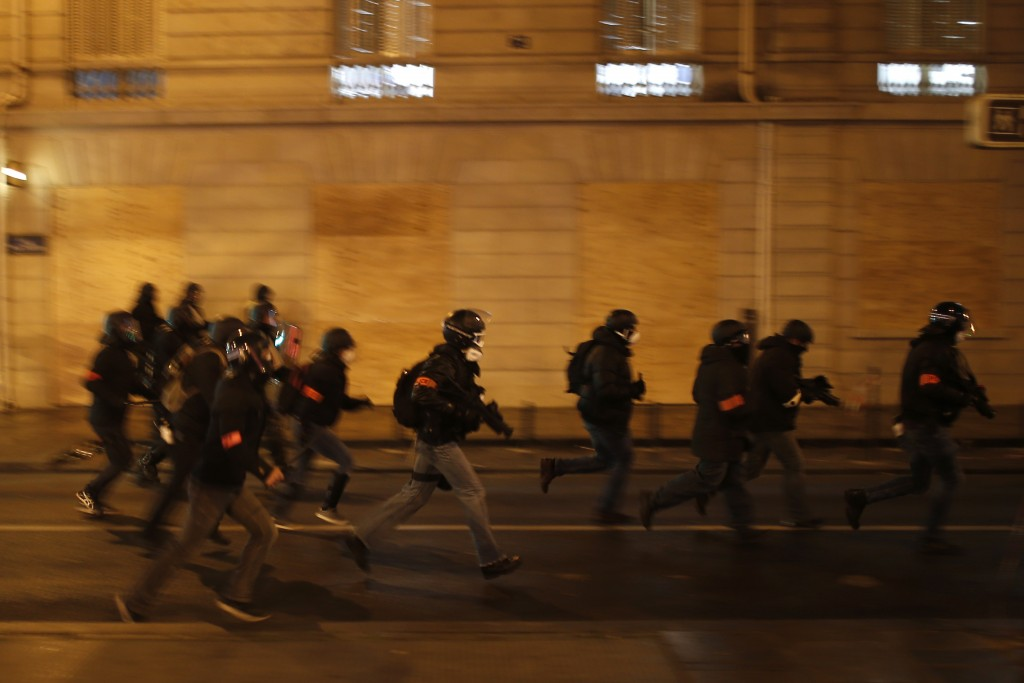 French riot police officers charge during clashes Saturday, Dec. 8, 2018 in Paris. Crowds of yellow-vested protesters angry at President Emmanuel Macr