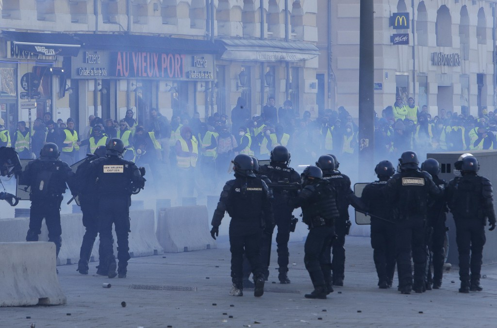 Riot police officers charge during clashes, Saturday, Dec. 8, 2018 in Marseille, southern France. The rumble of armored police trucks and the hiss of