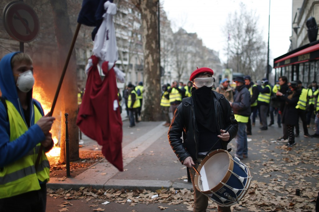 A demonstrator plays a drum Saturday, Dec. 8, 2018 in Paris. Crowds of yellow-vested protesters angry at President Emmanuel Macron and France's high t